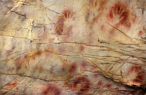 Handprints at the El Castillo cave in Spain, where paintings have been dated to as far back as 40,800 years ago. (Credit: Pedro Saura)